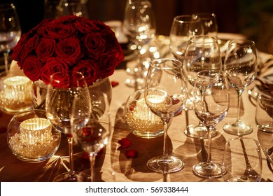 Red rose bouquet and candles around it stand on grey dinner table