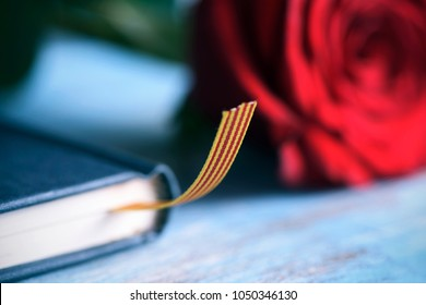 a red rose and a catalan flag on a book, on a blue table, for Sant Jordi, the Catalan name for Saint Georges Day, when it is tradition to give red roses and books in Catalonia, Spain