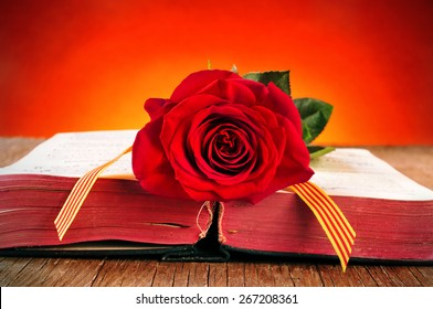 a red rose and the catalan flag on an old book for Sant Jordi, the Saint Georges Day, when it is tradition to give red roses and books in Catalonia, Spain