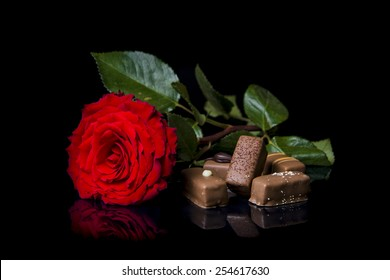 Red rose and chocolate on black background.