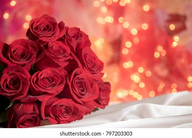 Red rose dozen bouquet with romantic warm glow flirty background and satin sheet, copy space