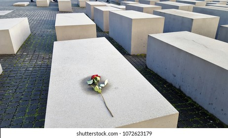 A red rose flower  left on a plaque of the Holocaus Mahnmal. BERLIN, GERMANY – December 4, 2017: View of Jewish Holocaust Memorial,