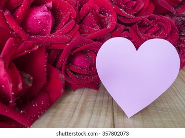 Red rose flower and pink heart shape note paper on wood background, Love concept for Valentines Day