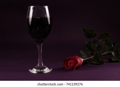 Red rose flower and wine glass on purple dark background, low key