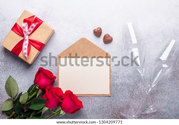 石の背景に赤いバラの花束、封筒、ギフトボックス、チョコレートスイーツバレンタインデーのグリーティングカードコピースペース上面