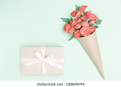 Red rose flowers, gift box or present on green table. Present with flower Greeting for Womens or Mothers Day. Top view, above. Flat lay