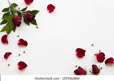 red rose flowers and leaf arrangement flat lay style on background white wooden