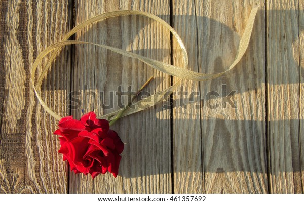 red rose with gold ribbon on the background of wooden boards