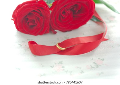 Red Rose and Gold ring on the table. Symbol of love. Valentine's Day concept. Soft focus, please selective focus of image.