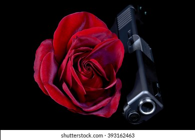 red rose with gun closeup on black background