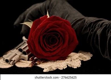 Red Rose with handgun, bullets and  hand in black glove on black background