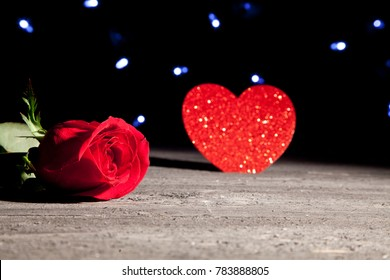 red rose and heart in dramatic lighting on barn wood planks with stars in the background.  Shallow depth of field with focus on the rose.
