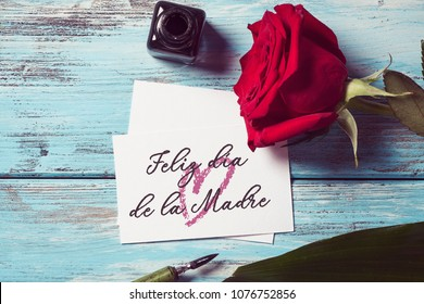 a red rose, an ink bottle, a nib pen and a piece of paper with the text feliz dia de la madre, happy mothers day written in spanish, on a blue rustic wooden table