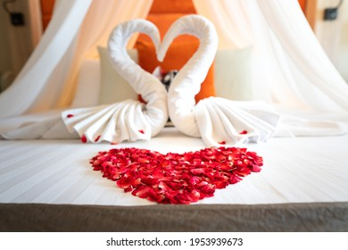 Red rose lobes in heart shape on white bed, with couple of swan as background. Interior decoration for lovely honeymoon suite room, abstract.