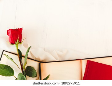 Red rose next to open books and closed books on white background. Perfect for Sant Jordi or for Valentine's Day.