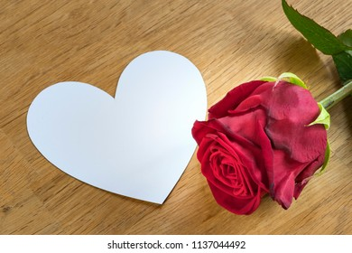 red rose on a table with white heart