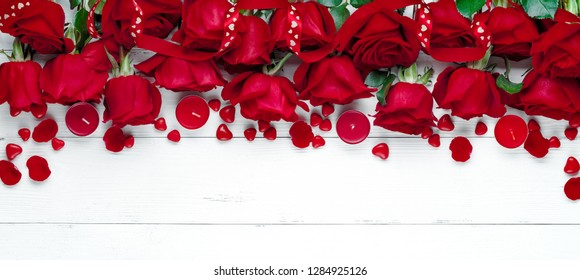 Red rose on white wooden table