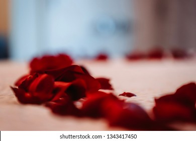 Red Rose petals (heart) across bed with bokeh