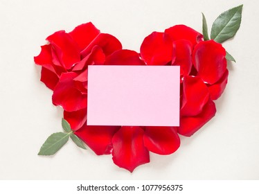 Red rose petals heart and card with text space flat lay.Love letter, romantic greeting card.