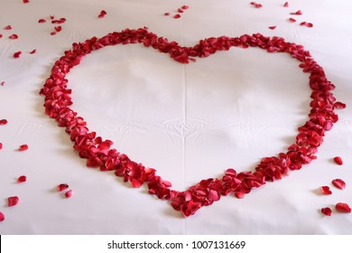 Red rose petals  heart on the bed, Decoration for Valentine's day.