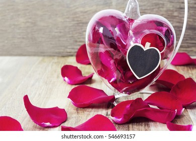 Red rose petals in heart vase on wooden background