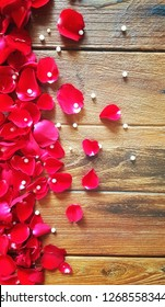 Red rose petals and pearl frame on wood table with space for background decoration on Valentine's day and wedding event.