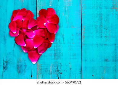 Red rose petals in the shape of heart on rustic antique teal blue wood background;  Valentine's Day, Mother's Day and love concept with painted wooden copy space