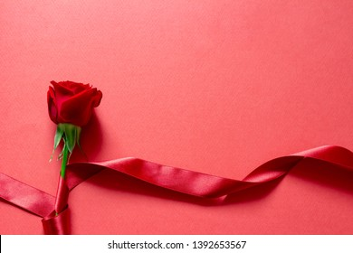It is a red rose with a red ribbon on a red plain background. It is an image of a gift with love.