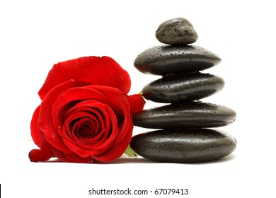 Red rose and spa black stones isolated on white background