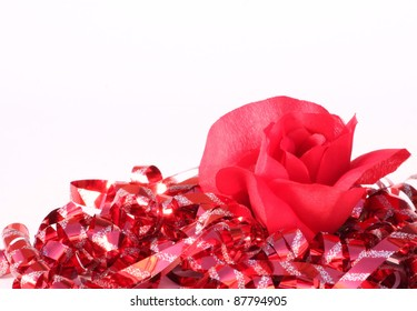 Red rose surrounded by red holiday ribbon with silver sparkles.