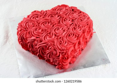 Red rose swirl cream cheese decoration on love shape cake