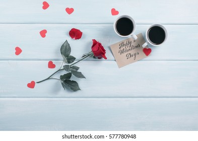 Red rose and two coffee cups with hearts and paper greeting or invitational card for Valentine day with place for text on background of shabby wooden planks. Copy space.