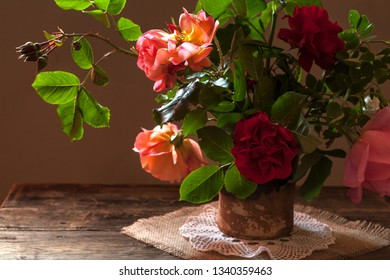 Red rose in vase on wooden table