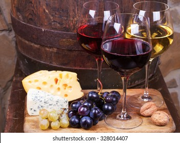 Red, rose and white glasses and bottles of wine. Grape, nuts, cheese and old wooden barrel
