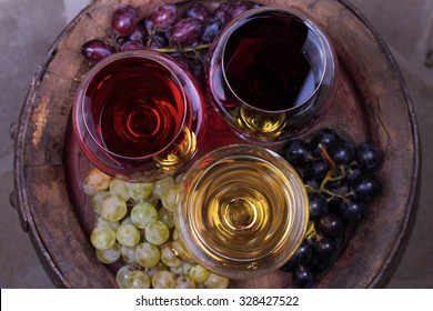 Red, rose and white glasses of wine with grape on old wooden barrel. View from above, top studio shot
