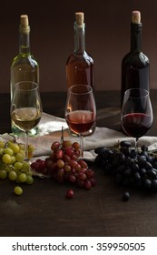 Red, rose and white wine bottles with three wineglasses and grapes on brown wood textured table covered with canvas towel