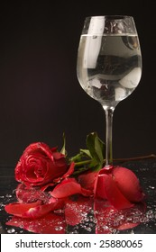 Red rose and wineglass of water on black background