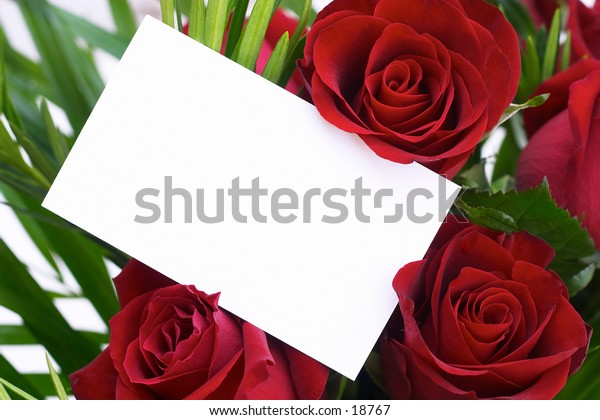 Red roses in a bouquet with a blank gift card