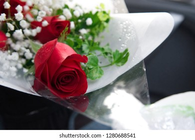 Red roses bouquet, floristry art, arranging blossom with paper and plastic wrapper for special occasions such as wedding and valentines day