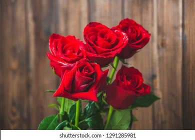 Red roses bouquet on brown wooden background