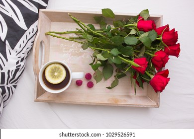 Red roses bouquet and tray with tea on the bed
