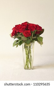 Red roses bouquet in vase on linen canvas background ( Valentine's day wishes )