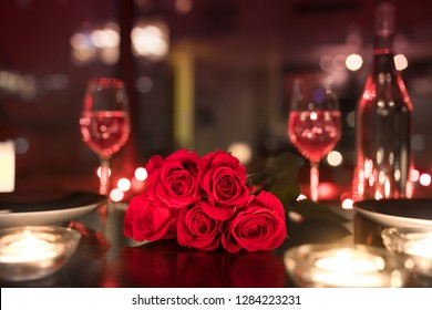 Red roses and candle lights in a romantic restaurant setting.
