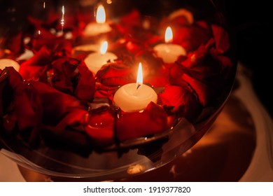 red roses and candles. flower petals in the water. a romantic date.