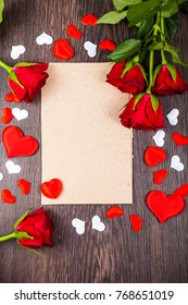 Red roses and card on a  wooden background. Greeting card with Valentine's Day, Birthday or Wedding.