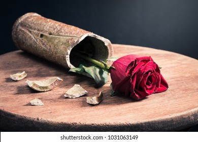 red roses in ceramic broken cylinder shape fell vase on the old wooden table with dark background