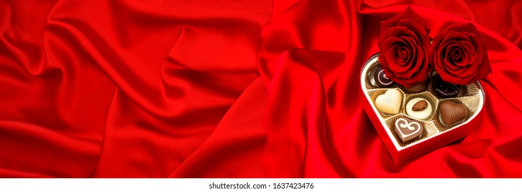 Red roses and chocolate pralines heart on satin background