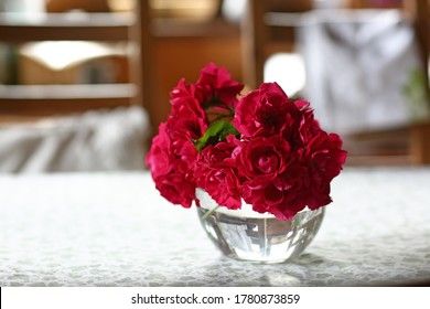 red roses in crystal vase on white table on kitchen interior close up photo