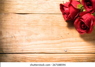 Red roses flowers on a vintage wooden planks background, greeting card and invitation cards