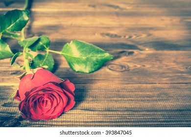 Red roses flowers on wooden background, vintage photo with copy space